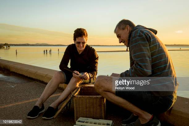 mature woman & mature man fishing - thisisaustralia stock pictures, royalty-free photos & images