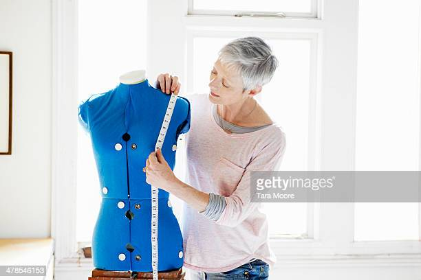 mature woman measuring dress form - short hair stock pictures, royalty-free photos & images