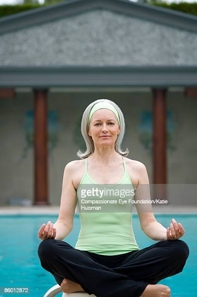 Mature woman meditating by pool