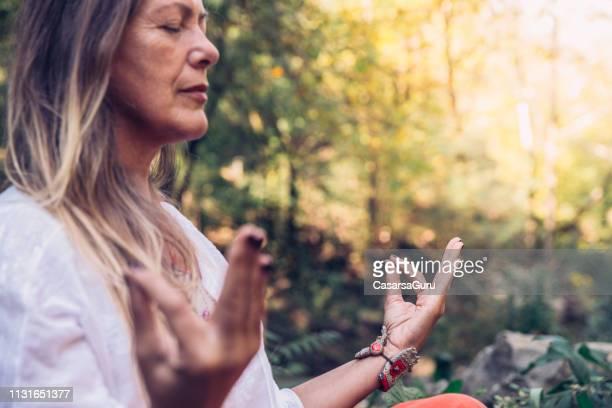 森の中で瞑想成熟した女性 - ヒッピー ストックフォトと画像