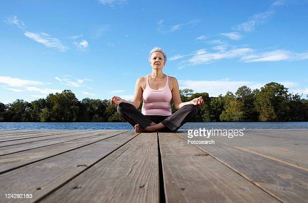 mature woman meditating in lotus position (low angle view) - low angle view photos et images de collection