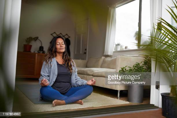 mature woman meditating while practicing yoga in her living room - meditating stock pictures, royalty-free photos & images