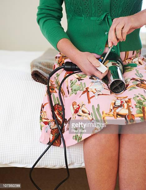 mature woman mending hairdryer