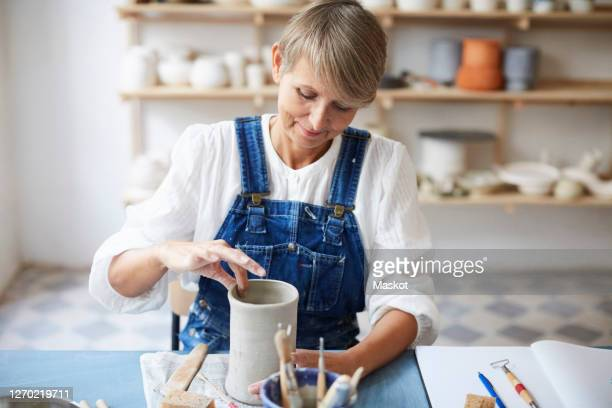 mature woman molding earthenware at table in art class - pottery stock pictures, royalty-free photos & images