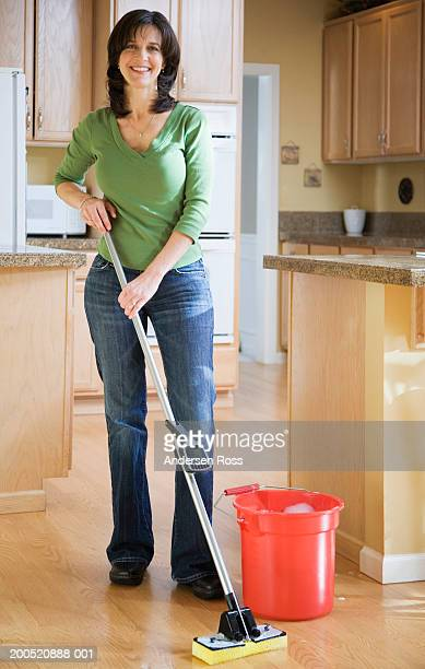 Mature woman mopping kitchen floor, smiling, portrait