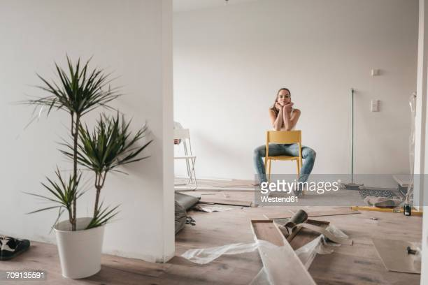 Mature woman moving house, sitting on chair