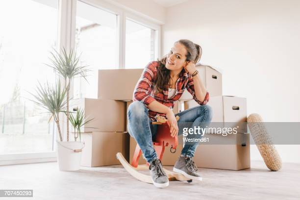 Mature woman moving house, sitting on rocking horse