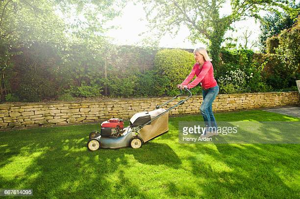 mature woman mowing sunlit garden lawn with lawn mower - lawn stock pictures, royalty-free photos & images
