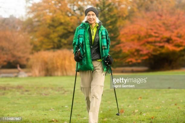 mature woman nordic walking in park - sigrid gombert stock-fotos und bilder