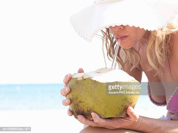 Mature woman on beach drinking coconut milk with straw (focus on foreground)