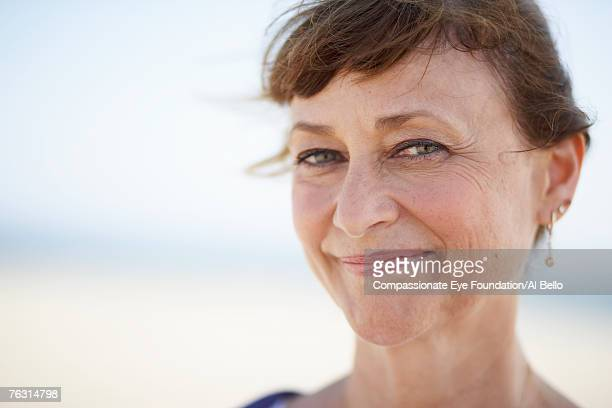Mature woman on beach, smiling, portrait, close-up
