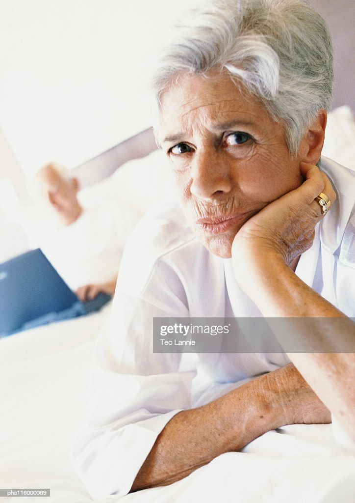 Mature woman on bed with hand under chin, portrait : Stockfoto