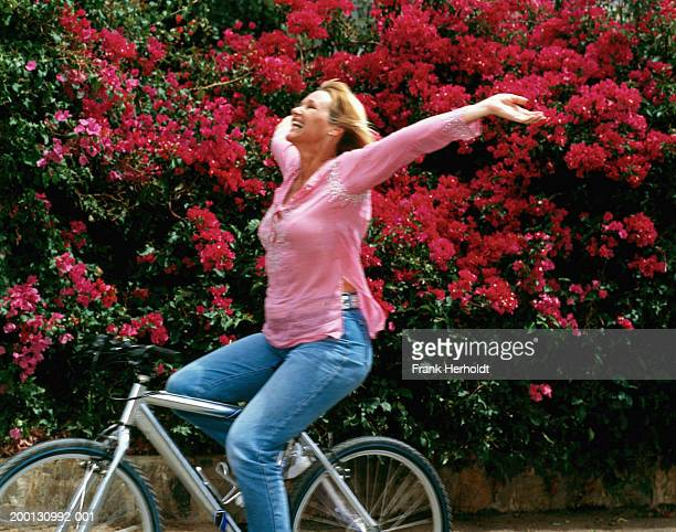 mature woman on bicycle, arms outstretched (blurred motion) - ecstatic stock pictures, royalty-free photos & images