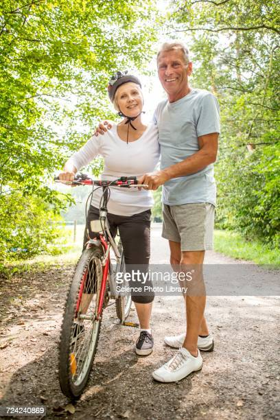 Mature woman on bike, Man with arm around
