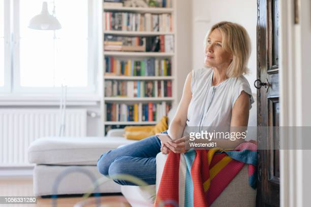 mature woman on couch at home holding cell phone - 50 54 years stock pictures, royalty-free photos & images