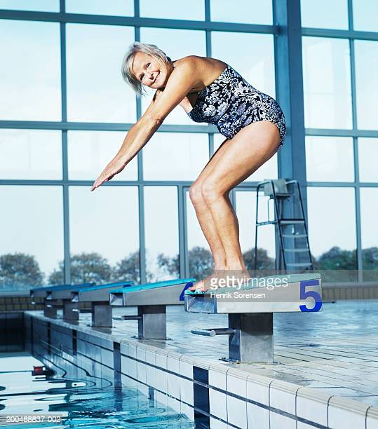 mature woman on diving board at swimming pool, portrait - alte frau badeanzug stock-fotos und bilder