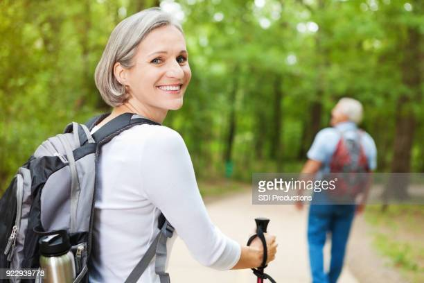 mature woman on hiking trip with husband - hiking pole stock pictures, royalty-free photos & images