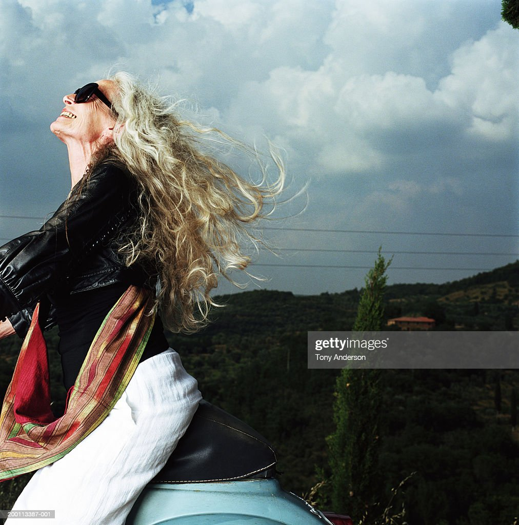 Mature woman on scooter, wind blowing through hair : Stock Photo