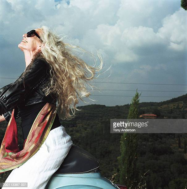 Mature woman on scooter, wind blowing through hair
