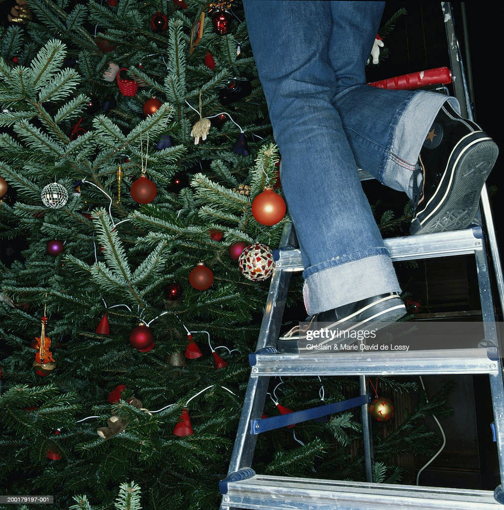 mature woman on step ladder decorating christmas tree low section stock photo