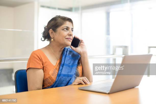 Mature woman on the phone in office with laptop