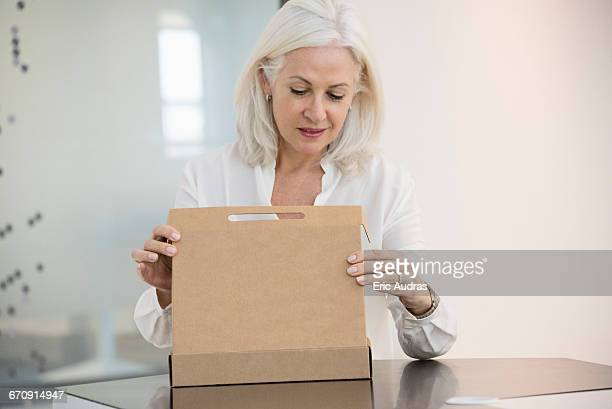 Mature woman opening a box at home