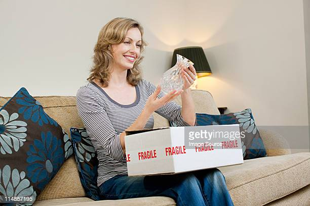 Femme d'âge mûr ouverture colis contenant des vases en verre