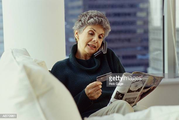 Mature woman ordering from catalog with credit card