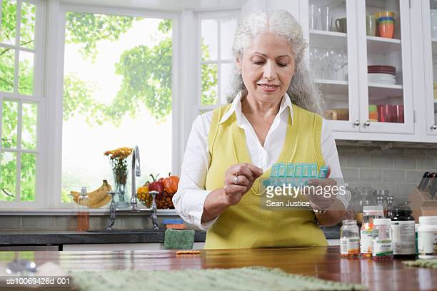 Mature woman organizing medicines into pill dispenser in kitchen
