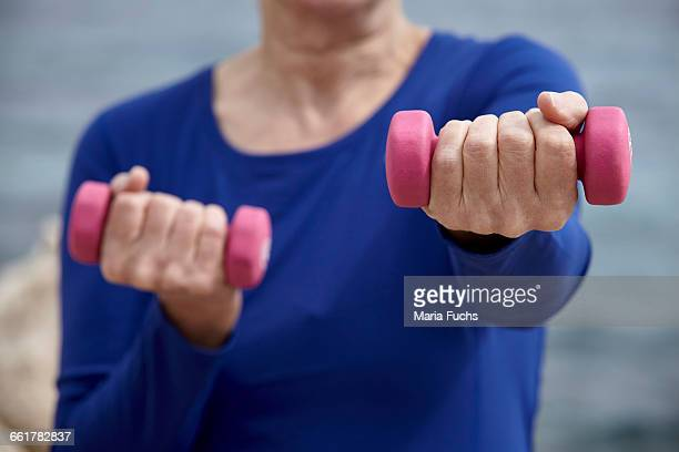 Mature woman outdoors, exercising with hand weights