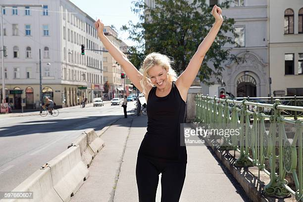mature woman outdoors wearing sports clothing arms raised looking down smiling - arme hoch stock-fotos und bilder