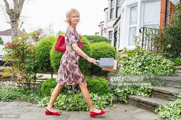 Mature woman outside home with shopping bags