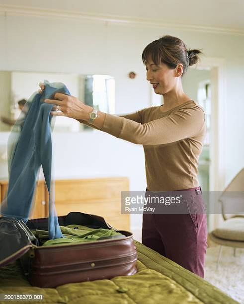Mature woman packing suitcase on bed, side view