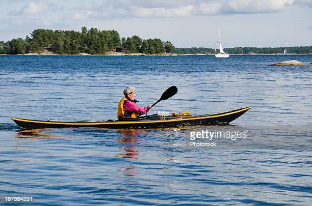 Mature woman paddling a black sea kayak