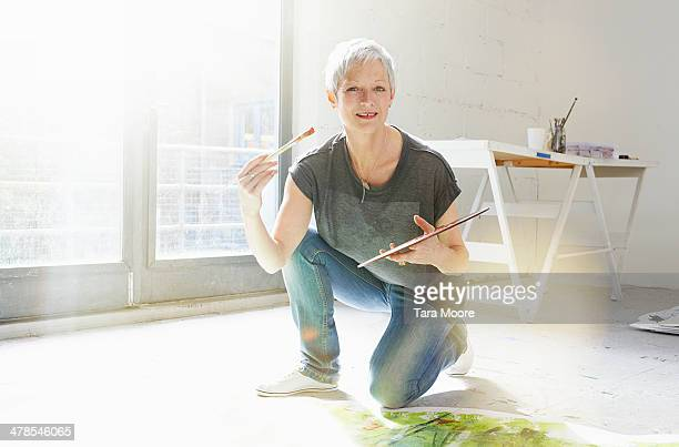 mature woman painting in studio - kneeling stock pictures, royalty-free photos & images
