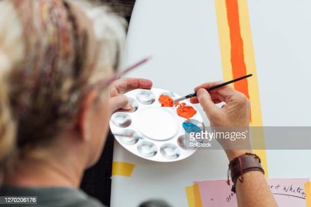 mature woman painting - pallet industrial equipment stock pictures, royalty-free photos & images