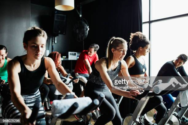 Mature woman participating in cycling class in fitness studio