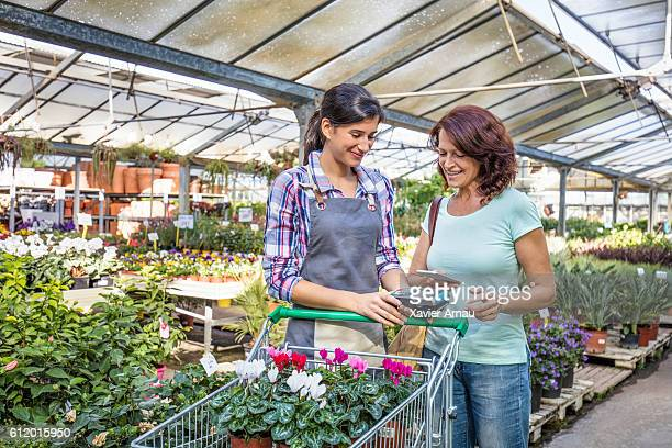 Mature woman paying by contactless mobile phone in garden store