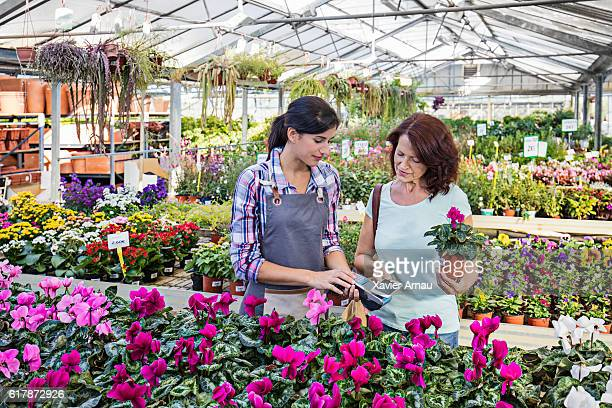 Mature woman paying for purchase in garden store