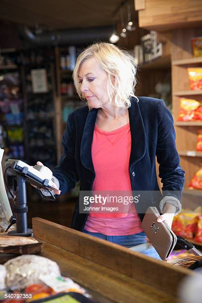 Mature woman paying for shopping