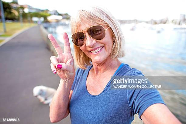 Mature woman peace sign with dog and sunglasses