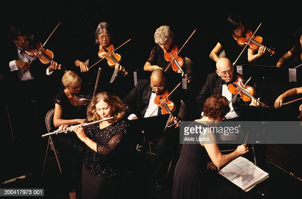 Mature woman performing flute solo with orchestra, overhead view
