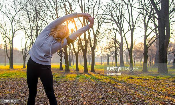 Mature Woman performs stretching before jogging