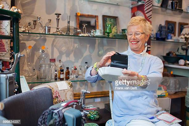 Mature woman photographing bowl with smartphone in vintage shop
