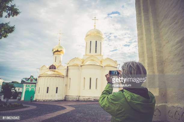 Mature Woman Photographing Church in Sergiyev Posad, city part of Golden Ring Cluster, Russia