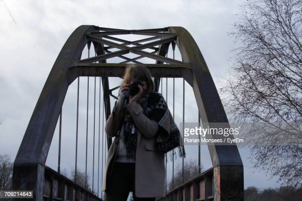 Mature Woman Photographing While Standing On Bridge Against Cloudy Sky