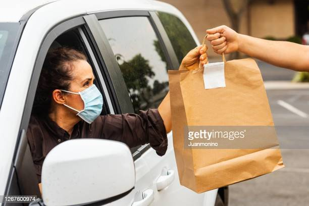 mature woman picking her to go order from her car at a curbside pickup - picking up stock pictures, royalty-free photos & images