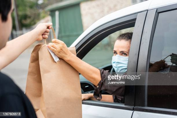 mature woman picking her to go order from her car at a curbside pickup - curbside pickup stock pictures, royalty-free photos & images