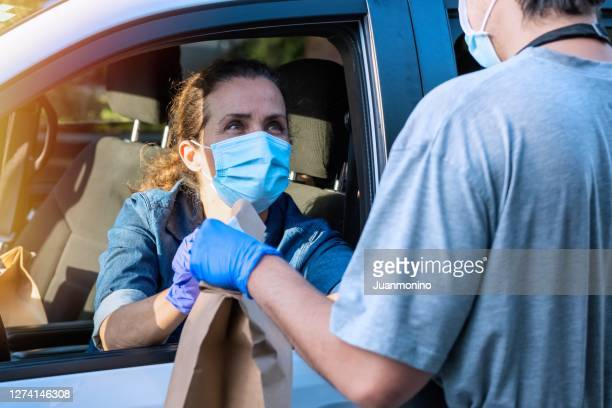 mature woman picking up her restaurant food from her car at a curbside pickup - curbside pickup stock pictures, royalty-free photos & images