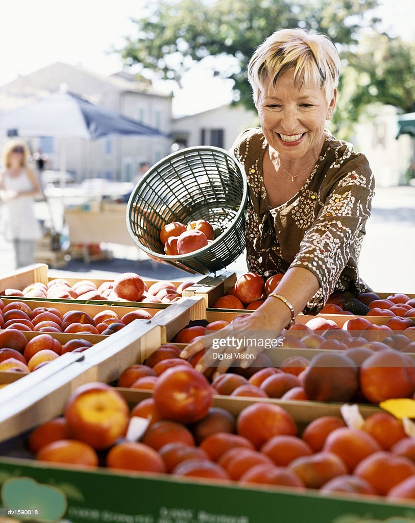 mature woman picks nectarines at an outdoor market in provence stock